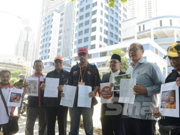 Mohd Noor Ali (tiga dari kiri) bersama NGO lain membuat laporan di Ibu Pejabat Polis Daerah Dang Wangi, di sini hari ini.