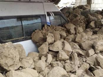 Sebuah kenderaan terperangkap di bawah runtuhan selepas gempa bumi menggegarkan sempadan Turki-Iran hari ini. - Foto Agensi
