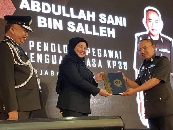 Haslina sambil diiringi Siful Yazan menyampaikan APC kepada warga Maqis pada majlis di Dewan Serbaguna MOA, Putrajaya.