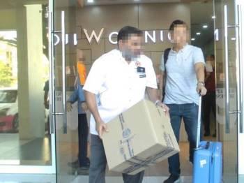 Pegawai JKN Pulau Pinang (kiri) membawa keluar barangan rampasan dari klinik yang didapati beroperasi tanpa lesen di Bayan Lepas kelmarin.