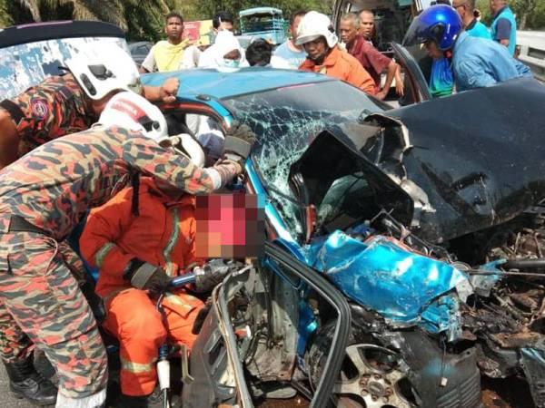 Anggota bomba mengeluarkan mayat mangsa. - Foto PDRM