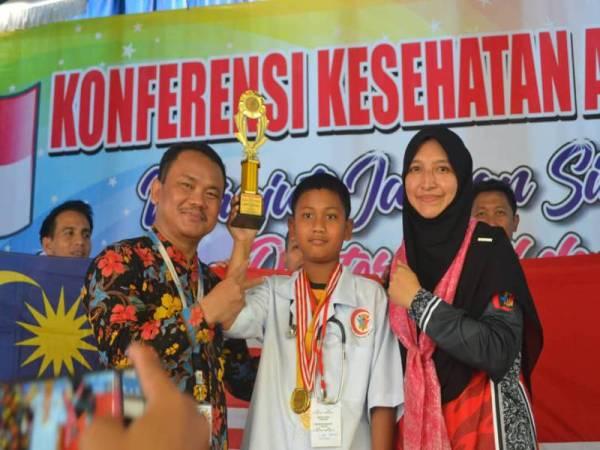 Ahmad Alif Syazwi Amizan (tengah) dipilih sebagai Ikon Doktor Muda pada Konvensyen Kesihatan Antarabangsa Kelab Doktor Muda Negeri Terengganu Malaysia bersama Dokter Kecil Sekolah Dasar Muhammadiyah 15 di Surabaya, Indonesia.