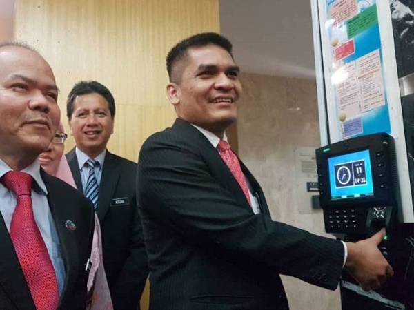 Mohd Radzi mengimbas cap jari pada mesin 'clock in' sebagai simbolik beliau melapor diri secara rasmi di Kementerian Pendidikan di Putrajaya hari ini.