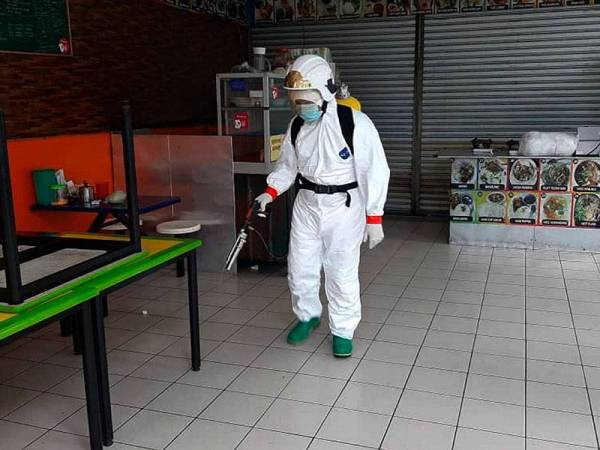 Anggota Bomba dan Penyelamat melakukan kerja-kerja nyahcemar di tiga pasaraya di Simpang Renggam dekat Kluang. - Foto Bernama