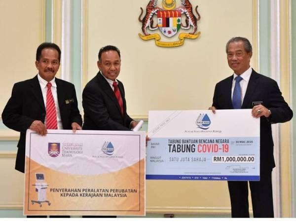 Perdana Menteri Tan Sri Muhyiddin Yassin (kanan) menerima sumbangan untuk Tabung COVID-19 daripada Puncak Niaga Holdings Berhad yang disampaikan oleh Pengerusi Eksekutifnya Tan Sri Rozali Ismail (tengah) pada majlis penyerahan sumbangan Tabung COVID-19 dari sektor korporat di Bangunan Perdana Putra hari ini.-fotoBERNAMA