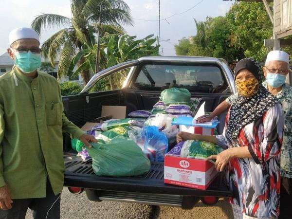 Yahya (kiri) menyerahkan bantuan keperluan asas kepada seorang penduduk di Kampung Tanjung Seri di sini semalam.