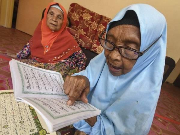 Siti Mariam (kanan) ditemani anaknya, Saudah sewaktu membaca al-Quran ketika ditemui Bernama di Kampung Pasir Golok Ketereh hari ini. - Foto Bernama