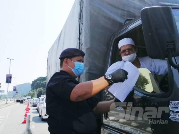 A Asmadi memeriksa surat kebenaran seorang pemandu lori ketika meninjau operasi sekatan jalan raya di Jalan Kuala Kangsar hari ini.