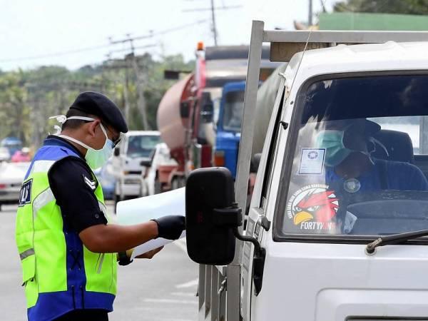 Anggota polis memeriksa dokumen perjalanan seorang pemandu sebelum membenarkannya lalu sewaktu operasi sekatan jalan raya berikutan arahan Perintah Kawalan Pergerakan yang memasuki fasa kedua hari ini.