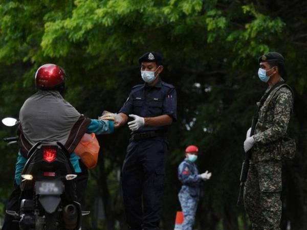 KUANTAN, 2 April -- HATI MULIA...Polis Diraja Malaysia (PDRM) bersama Angkatan Tentera Malaysia (ATM) menerima sumbangan makanan daripada penduduk yang menghargai jasa petugas keselamatan sebagai barisan hadapan dalam usaha mengekang penyebaran Covid-19 pada hari kedua Perintah Kawalan Pergerakan Fasa Kedua ketika tinjauan fotoBernama semalam. -fotoBERNAMA