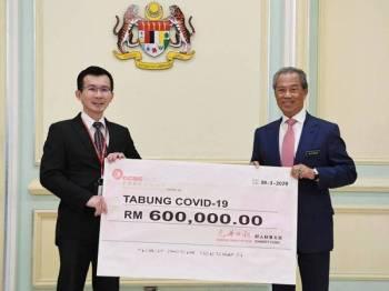 Perdana Menteri Tan Sri Muhyiddin Yassin menerima sumbangan daripada Pembantu Ketua Editor Kwong Wah Yit Poh Press Ng Yee Min pada Majlis Penyerahan Sumbangan Tabung COVID-19 dari sektor korporat di Bangunan Perdana Putra hari ini. - Foto Bernama