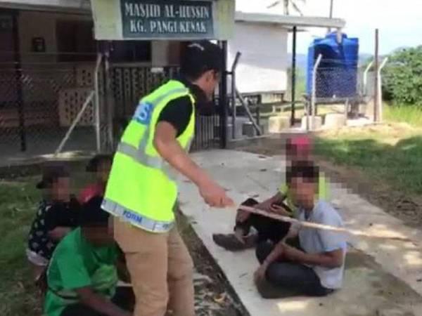 Gambar tular pegawai polis yang didakwa merotan lima remaja lelaki yang ingkar Perintah Kawalan Pergerakan (PKP) di Kunak, Sabah Rabu lalu.