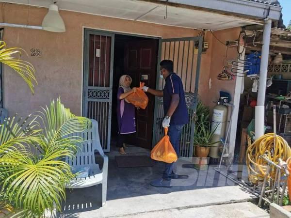 Arul Kumar mengagihkan sumbangan keperluan asas kepada penduduk setempat.