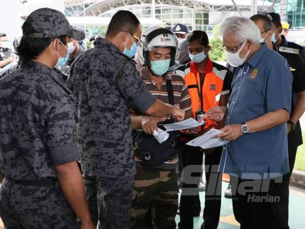 Hamzah (kanan) melakukan pemeriksaan terhadap seorang penunggang motosikal semasa melakukan lawatan di Kompleks Kastam, Imigresen dan Kuarantin (CIQ) Bangunan Sultan Iskandar (BSI), Johor Bahru hari ini.