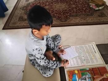 Anak yang paling bongsu berusia sembilan tahun khusyuk menyalin nota untuk sesi tazkirah selepas solat berjemaah.