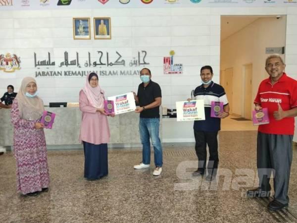Timbalan Ketua Pengarah (Dasar) Jakim, Hakimah Mohd Yusoff mewakili pihak Pusat Kuarantin Covid-19 di IKMAS, Sarawak dan ILIM, Besut menerima 40 naskhah wakaf al-Quran daripada pihak WUIF hari ini.