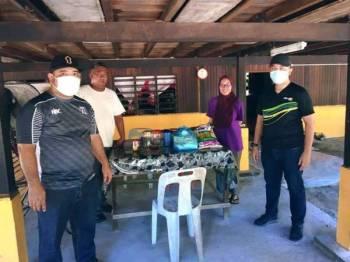 Mohd Imran (kanan) menyampaikan sumbangan kepada salah seorang penerima di DUN Sungai Panjang di sini.