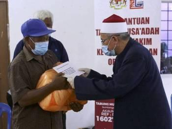 Dr Zulkifli Mohamad Al-Bakri (kanan) menyampaikan sumbangan barangan keperluan kepada masyarakat Orang Asli pada Misi Bantuan Tabung Musa'adah Covid-19 Jabatan Kemajuan Islam Malaysia (Jakim) ke Perkampungan Orang Asli di Kampung Tekir hari ini. - Foto Bernama