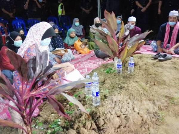 Ibu Allahyarham, Norriza Mat Sani, 53, menyiram air di pusara anaknya.