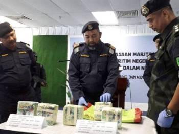 Sanifah (tengah) menunjukkan guni yang disorokkan dalam bungkusan plastik teh Cina yang ditinggalkan dalam sebuah bot di muara Parit Jawa, Muar kelmarin.