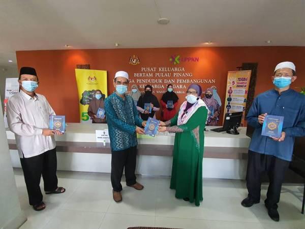 Mohd Taufek (dua dari kiri) memyampaikan naskhah al-Quran kepada Dr Azura.