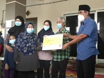 Dari kanan: Tarmizi dan Abd Rahim ketika penyerahan replika cek Faedah Pengurusan Jenazah kepada keluarga Zeti Haryanti (kiri)