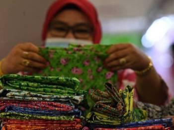 Peniaga Kompleks Pekan Rabu Asni Nyak Bakar menunjukkan sebahagian koleksi baju Kedah yang dijual di Kompleks Pekan Rabu di sini. - Foto Bernama