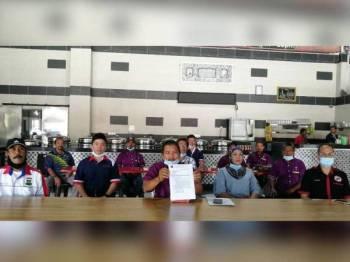 Jaafar (tengah) menunjukkan salinan surat permohonan pembukaan pasar malam yang dihantar kepada MKN dan Pejabat Menteri Besar Perak ketika sidang akhbar bersama beberapa persatuan yang lain di sini hari ini.