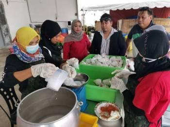 Ahmad Afandi (empat dari kiri) melihat pekerjanya membuat pembungkusan santan segar.
