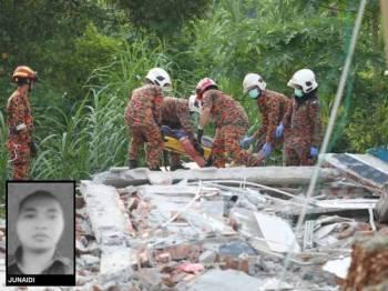 Anggota bomba mengeluarkan mangsa dari kawasan runtuhan.