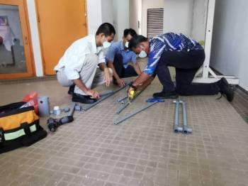 Mohamad Nizam dibantu dua rakan dari CUIC menghasilkan alat pemijak cecair pembasmi kuman.