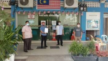 Kamaruzzaman (dua dari kanan) menunjukkan laporan polis yang dibuat di Balai Polis Pelangi Indah Johor Bahru Selatan petang tadi.