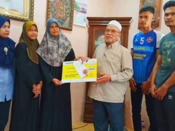 Rosni Wati (tiga dari kiri) bersama anak-anaknya menerima sumbangan daripada Perkeso dan Tabung Serambi Makkah yang disampaikan oleh Hanifa (tiga dari kanan) dan Nora (kiri) di rumahnya di Kampung Padang To' La di sini hari ini.