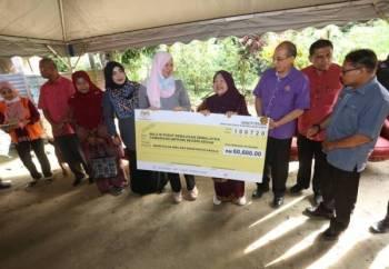 Rina menyampaikan 'mock cheque' kepada Rokiah (empat kanan) ketika melakukan kunjungan ke Kampung Sungai Tembak B hari ini.