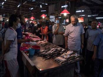 Annuar (dua, kanan) beramah mesra bersama peniaga-peniaga ketika membuat lawatan di Pasar Dato Keramat hari ini.- Foto Bernama