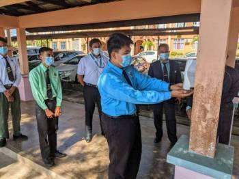 Salah seorang pelajar sekolah menengah menggunakan cecair sanitasi tangan sumbangan Petronas.