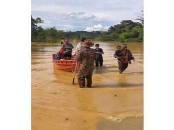 Anggota bomba membantu memindahkan mangsa banjir ke pusat pemindahan. - Foto ihsan bomba