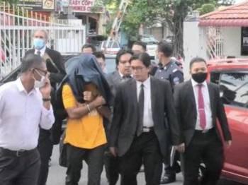 Suspek (dua dari kiri) ketika tiba di Mahkamah Majistret Kangar hari ini.