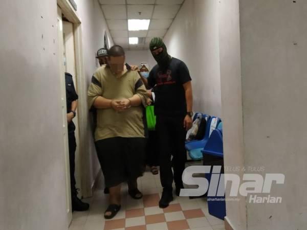 Anggota polis mengiringi tertuduh yang dihadapkan ke Mahkamah Sesyen Johor Bahru hari ini atas pertuduhan di bawah Akta Anti Pemerdagangan Orang dan Anti Penyeludupan Migran 2007.