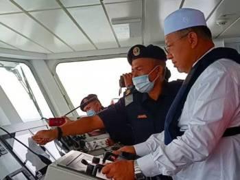 Ahmad (kanan) menunjukkan kemahiran mengemudi KM Tok Bali ketika merasmikan KM Tok Bali di Jeti Tok Bali Supply Base.