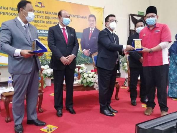 Sulaiman (dua dari kanan) menyampaikan sijil penghargaan kepada salah seorang sukarelawan pada majlis di Melaka hari ini.