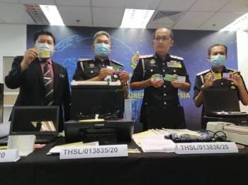 Khairul Dzaimee (dua dari kanan) menunjukkan kad yang dipalsukan oleh sindiket pada sidang akhbar di Pejabat Imigresen Putrajaya hari ini.