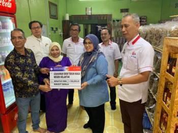 Mas Ermieyati (dua dari kanan) menyerahkan replika cek kepada Meriam ketika melawat kedainya di Kampung Badang, Kota Bharu hari ini.