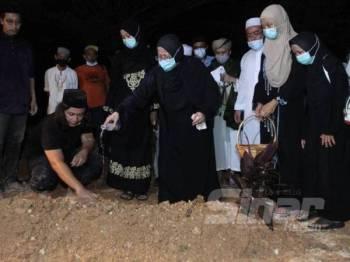 Sharifah Nooraiya menyiram kubur Allahyarham Datuk Abdul Jalil Ali dengan air mawar sambil diperhatikan anak dan saudara-mara.
