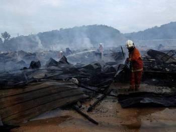 Anggota Jabatan Bomba dan Penyelamat (JBPM) Negeri Sembilan dilihat sibuk melakukan kerja-kerja pemadaman api dan pemeriksaan di kawasan rumah kongsi yang musnah akibat kebakaran di Jalan Labu LBJ Taman Gadong Jaya hari ini. Foto: Bernama