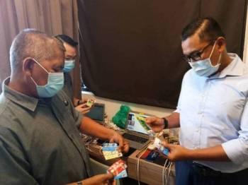 Mohd Zani (kiri) menunjukkan barangan yang dirampas dalam serbuan di sebuah kondominium di Kuala Lumpur hari ini.