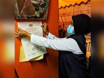 Pegawai penguat kuasa JKN Pahang menampal notis arahan tutup terhadap premis makanan yang didapati berada dalam keadaan kotor hasil pemeriksaan dalam Operasi Caras Hijau Bersepadu di Cameron Highlands kelmarin. - Foto ihsan JKN Pahang