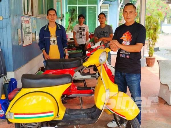 Tuan Mohd Arif (hadapan) dan anak-anaknya menunjukkan koleksi Vespa yang dimiliki mereka.