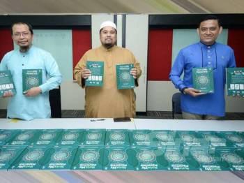 Fazrul (kiri), Tirmizi (tengah) dan Tarmizi menunjukkan buku Nota My#Quran Time selepas majlis menandatangani buku tersebut di Kumpulan Karangkraf, Shah Alam semalam.