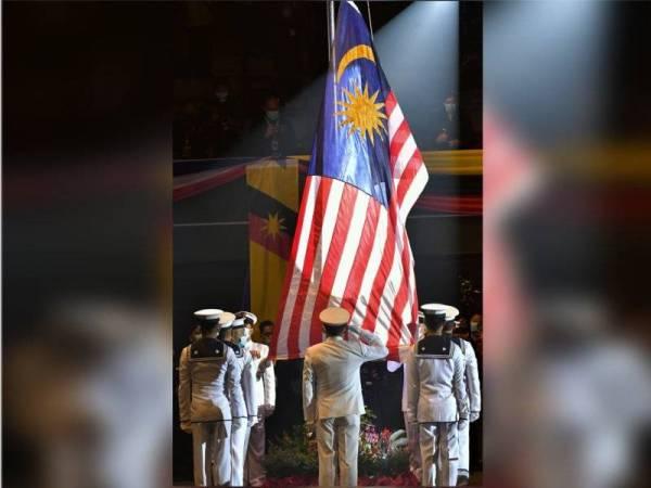 Para pegawai dan anggota Tentera Laut Diraja Malaysia (TLDM) menaikkan Jalur Gemilang pada Majlis Sambutan Hari Malaysia di Stadium Tertutup Sibu hari ini. - Foto Bernama